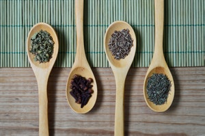 dried herbs arranged on spoons
